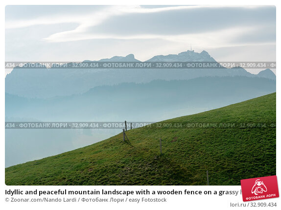Idyllic and peaceful mountain landscape with a wooden fence on a grassy hillside and a great view of the Alpstein mountains and Appenzell region in the Swiss Alps behind. Стоковое фото, фотограф Zoonar.com/Nando Lardi / easy Fotostock / Фотобанк Лори