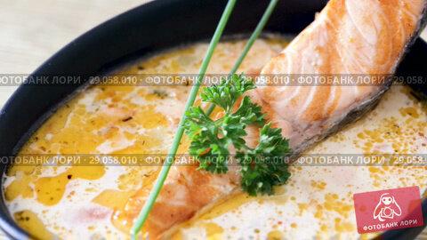 Купить «Image of tasty cream soup with salmon, served with greens in bowl at table», видеоролик № 29058010, снято 27 августа 2018 г. (c) Яков Филимонов / Фотобанк Лори