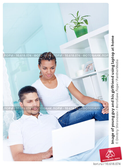 Image of young guy and his girlfriend using laptop at home. Стоковое фото, фотограф Dmitriy Shironosov / PantherMedia / Фотобанк Лори