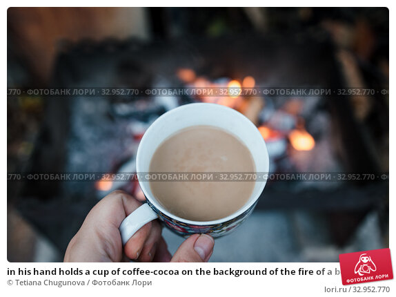 in his hand holds a cup of coffee-cocoa on the background of the fire of a bonfire in the grill. Autumn retro mood. View from above. Copy space. Selective focus, blur. Стоковое фото, фотограф Tetiana Chugunova / Фотобанк Лори