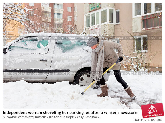 Independent woman shoveling her parking lot after a winter snowstorm. Стоковое фото, фотограф Zoonar.com/Matej Kastelic / easy Fotostock / Фотобанк Лори