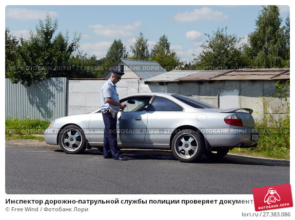 Купить «Инспектор дорожно-патрульной службы полиции проверяет документы водителя автомобиля», фото № 27383086, снято 12 августа 2017 г. (c) Free Wind / Фотобанк Лори