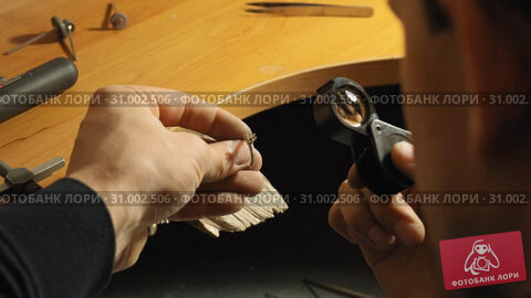 Jewerly master watches on the metal ring through the magnifying glass slow motion. Стоковое видео, видеограф Denis Mishchenko / Фотобанк Лори