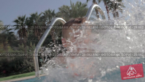 Купить «Joyful kid splashing water in swimming pool outdoor», видеоролик № 29082886, снято 19 сентября 2018 г. (c) Данил Руденко / Фотобанк Лори