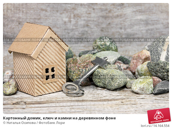 Купить «Картонный домик, ключ и камни на деревянном фоне», фото № 14164554, снято 30 ноября 2015 г. (c) Наталья Осипова / Фотобанк Лори