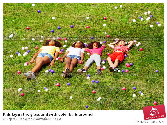 Kids lay in the grass and with color balls around. Стоковое фото, фотограф Сергей Новиков / Фотобанк Лори