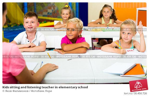Kids sitting and listening teacher in elementary school. Стоковое фото, фотограф Яков Филимонов / Фотобанк Лори