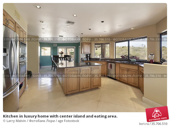Kitchen in luxury home with center island and eating area. Редакционное фото, фотограф Larry Malvin / age Fotostock / Фотобанк Лори