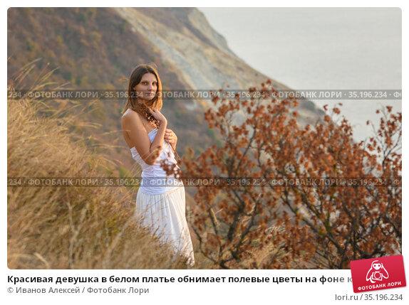 Красивая девушка в белом платье обнимает полевые цветы на фоне красивого пейзажа. Стоковое фото, фотограф Иванов Алексей / Фотобанк Лори