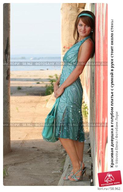 Красивая девушка в голубом платье с сумкой в руке стоит около стены, фото № 58962, снято 6 июля 2007 г. (c) Vdovina Elena / Фотобанк Лори