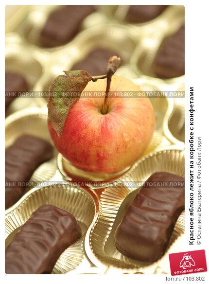 Красное яблоко лежит на коробке с конфетами, фото № 103802, снято 20 октября 2016 г. (c) Останина Екатерина / Фотобанк Лори
