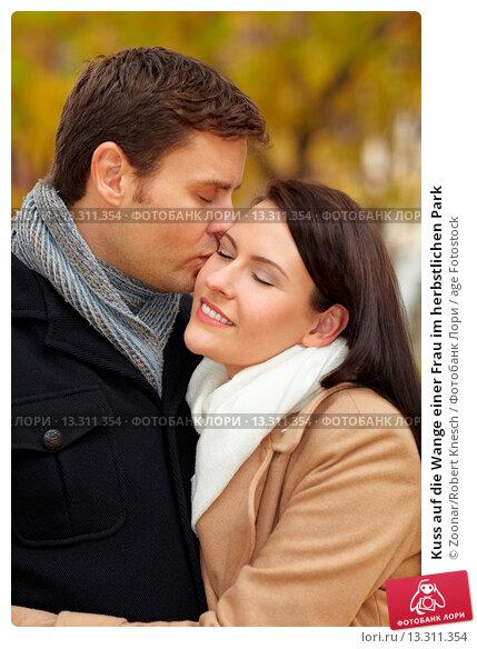 Kuss auf die Wange einer Frau im herbstlichen Park