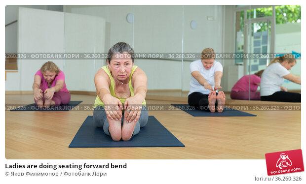 Ladies are doing seating forward bend. Стоковое фото, фотограф Яков Филимонов / Фотобанк Лори