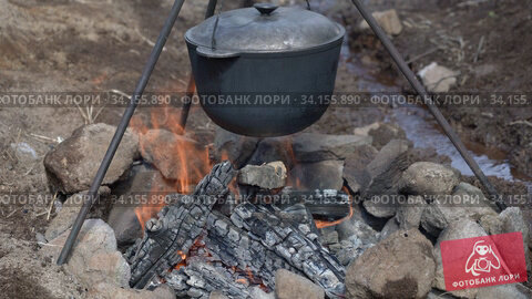 Large black cast-iron pot hangs on tripod above burning bonfire on field kitchen. Cooking outdoors, on camping trip, during picnic. Стоковое видео, видеограф А. А. Пирагис / Фотобанк Лори