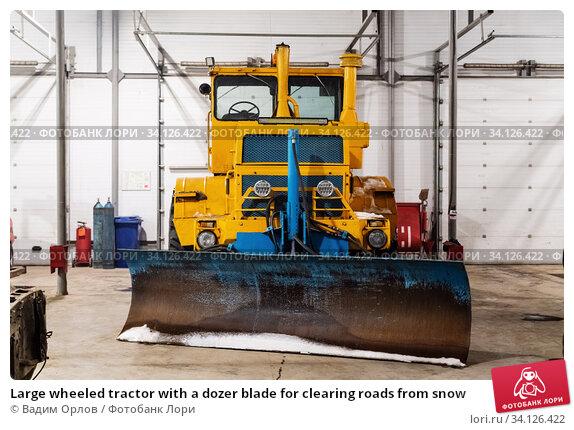 Купить «Large wheeled tractor with a dozer blade for clearing roads from snow», фото № 34126422, снято 16 декабря 2019 г. (c) Вадим Орлов / Фотобанк Лори
