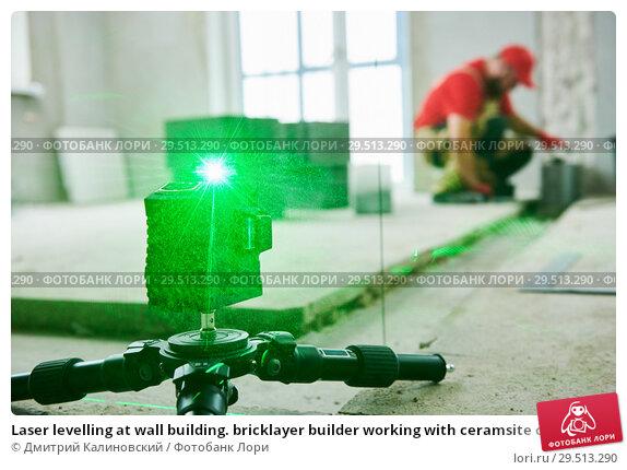 Купить «Laser levelling at wall building. bricklayer builder working with ceramsite concrete blocks», фото № 29513290, снято 24 сентября 2018 г. (c) Дмитрий Калиновский / Фотобанк Лори