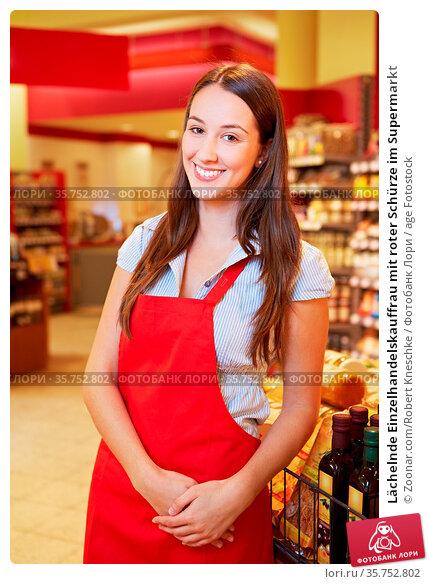 Lächelnde Einzelhandelskauffrau mit roter Schürze im Supermarkt. Стоковое фото, фотограф Zoonar.com/Robert Kneschke / age Fotostock / Фотобанк Лори