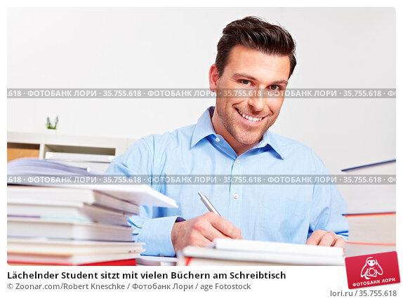Lächelnder Student sitzt mit vielen Büchern am Schreibtisch. Стоковое фото, фотограф Zoonar.com/Robert Kneschke / age Fotostock / Фотобанк Лори