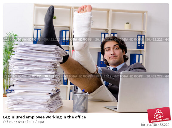 Leg injured employee working in the office. Стоковое фото, фотограф Elnur / Фотобанк Лори