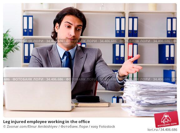 Leg injured employee working in the office. Стоковое фото, фотограф Zoonar.com/Elnur Amikishiyev / easy Fotostock / Фотобанк Лори