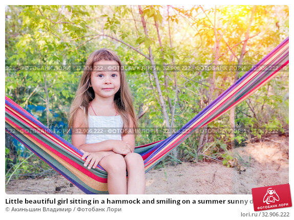 Little beautiful girl sitting in a hammock and smiling on a summer sunny day. Стоковое фото, фотограф Акиньшин Владимир / Фотобанк Лори