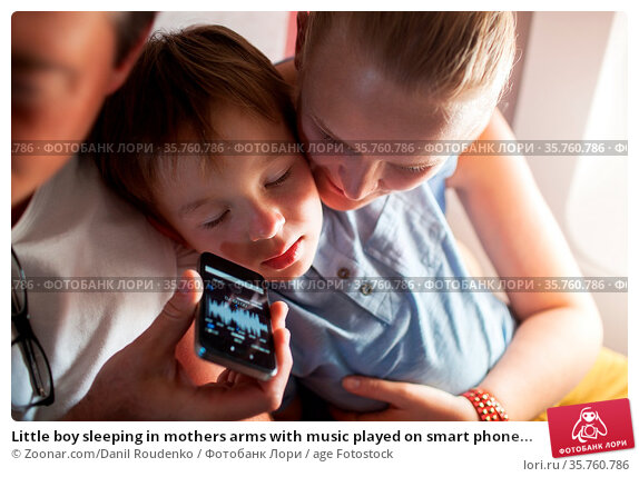 Little boy sleeping in mothers arms with music played on smart phone... Стоковое фото, фотограф Zoonar.com/Danil Roudenko / age Fotostock / Фотобанк Лори