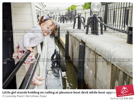 Купить «Little girl stands holding on railing at pleasure boat deck while boat approach pier», фото № 25838458, снято 19 ноября 2019 г. (c) Losevsky Pavel / Фотобанк Лори