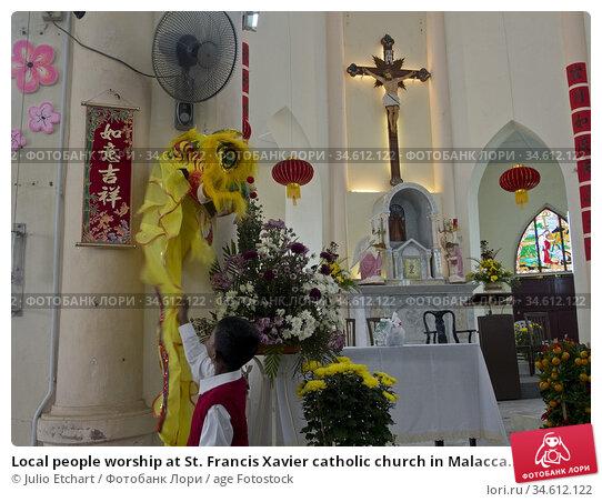 Local people worship at St. Francis Xavier catholic church in Malacca... (2014 год). Редакционное фото, фотограф Julio Etchart / age Fotostock / Фотобанк Лори