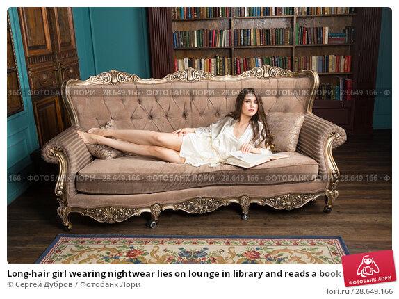 Купить «Long-hair girl wearing nightwear lies on lounge in library and reads a book», фото № 28649166, снято 1 апреля 2018 г. (c) Сергей Дубров / Фотобанк Лори