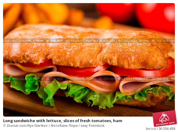 Long sandwiche with lettuce, slices of fresh tomatoes, ham. Стоковое фото, фотограф Zoonar.com/Ilya Starikov / easy Fotostock / Фотобанк Лори