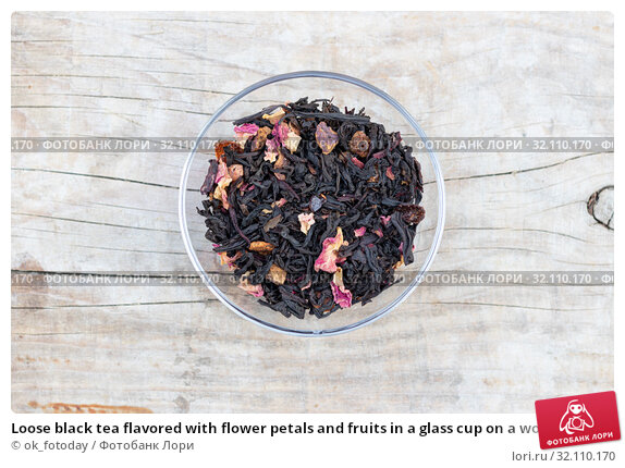 Купить «Loose black tea flavored with flower petals and fruits in a glass cup on a wooden background top view», фото № 32110170, снято 23 августа 2019 г. (c) ok_fotoday / Фотобанк Лори
