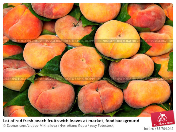Lot of red fresh peach fruits with leaves at market, food background. Стоковое фото, фотограф Zoonar.com/Liubov Mikhailova / easy Fotostock / Фотобанк Лори