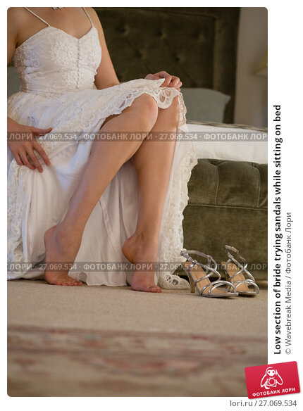 Low section of bride trying sandals while sitting on bed, фото № 27069534, снято 2 мая 2017 г. (c) Wavebreak Media / Фотобанк Лори