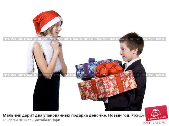 Мальчик дарит два упакованных подарка девочке. Новый год. Рождество, фото № 314750, снято 25 ноября 2007 г. (c) Сергей Лешков / Фотобанк Лори