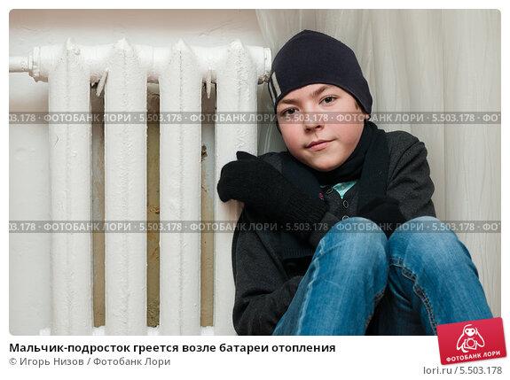 Купить «Мальчик-подросток греется возле батареи отопления», эксклюзивное фото № 5503178, снято 10 января 2014 г. (c) Игорь Низов / Фотобанк Лори