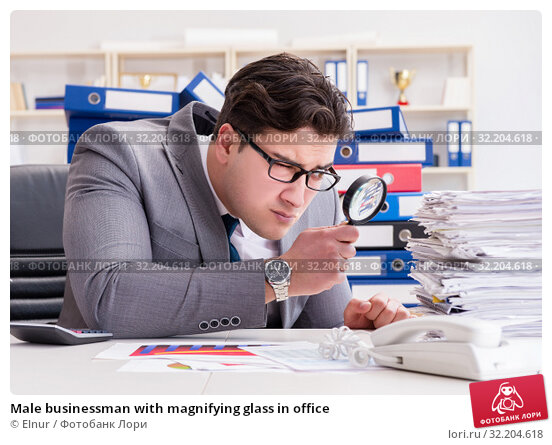 Male businessman with magnifying glass in office. Стоковое фото, фотограф Elnur / Фотобанк Лори