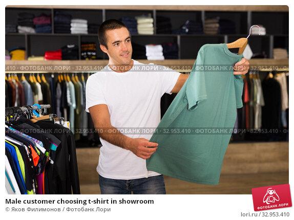 Male customer choosing t-shirt in showroom. Стоковое фото, фотограф Яков Филимонов / Фотобанк Лори