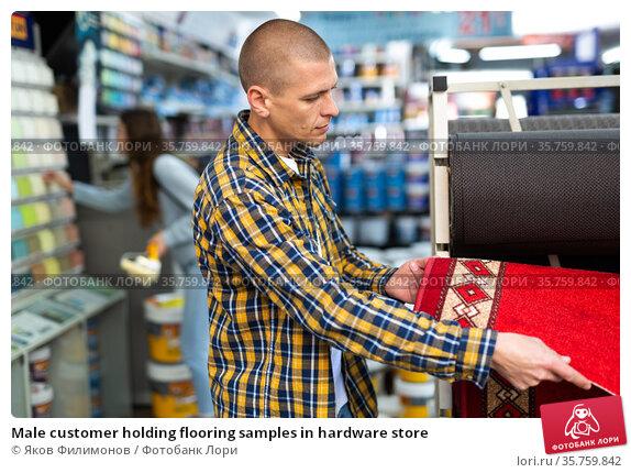 Male customer holding flooring samples in hardware store. Стоковое фото, фотограф Яков Филимонов / Фотобанк Лори