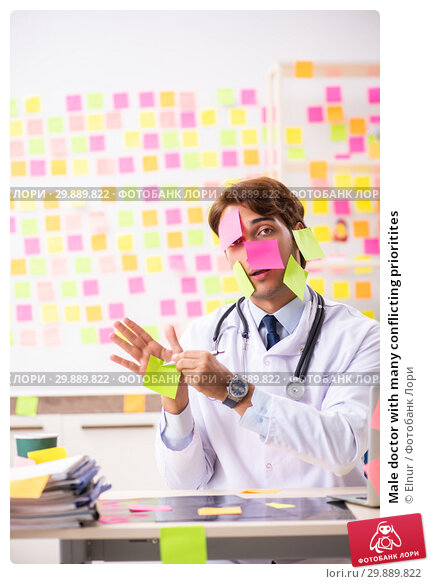 Купить «Male doctor with many conflicting prioritites», фото № 29889822, снято 17 августа 2018 г. (c) Elnur / Фотобанк Лори