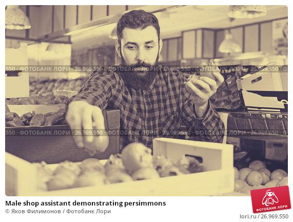 Купить «Male shop assistant demonstrating persimmons», фото № 26969550, снято 15 ноября 2016 г. (c) Яков Филимонов / Фотобанк Лори