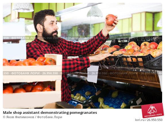 Купить «Male shop assistant demonstrating pomegranates», фото № 26950550, снято 15 ноября 2016 г. (c) Яков Филимонов / Фотобанк Лори