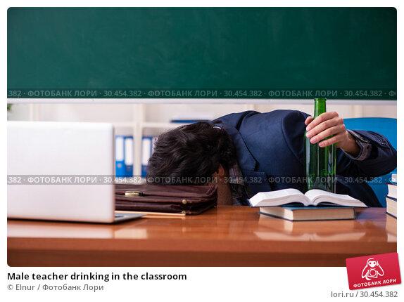Male teacher drinking in the classroom. Стоковое фото, фотограф Elnur / Фотобанк Лори