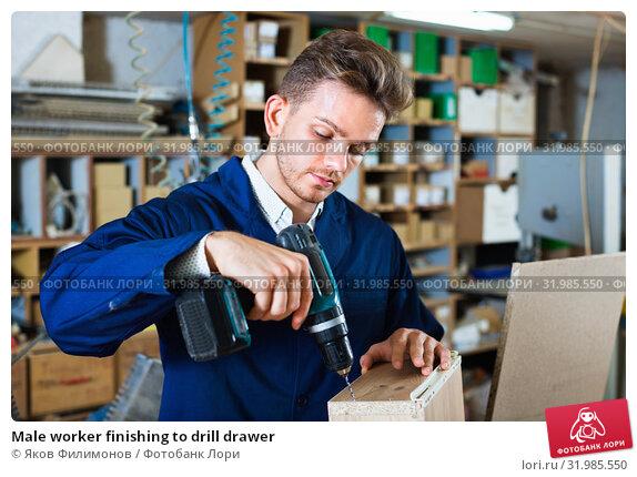 Купить «Male worker finishing to drill drawer», фото № 31985550, снято 7 ноября 2016 г. (c) Яков Филимонов / Фотобанк Лори