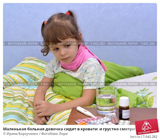 Маленькая больная девочка сидит в кровати  и грустно смотрит на лекарства. Стоковое фото, фотограф Ирина Борсученко / Фотобанк Лори