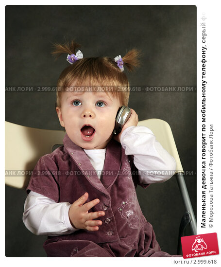 Маленькая девочка говорит по мобильному телефону, серый фон. Стоковое фото, фотограф Морозова Татьяна / Фотобанк Лори