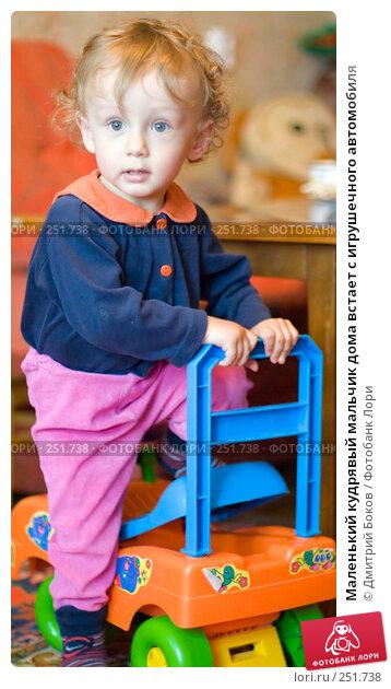 Маленький кудрявый мальчик дома встает с игрушечного автомобиля, фото № 251738, снято 13 мая 2006 г. (c) Дмитрий Боков / Фотобанк Лори