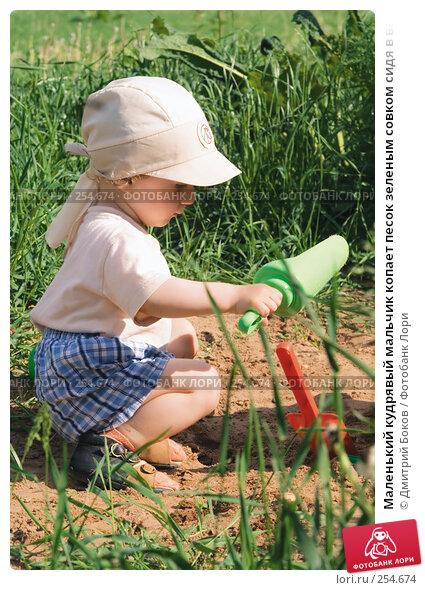 Маленький кудрявый мальчик копает песок зеленым совком сидя в высокой траве, фото № 254674, снято 3 июня 2006 г. (c) Дмитрий Боков / Фотобанк Лори