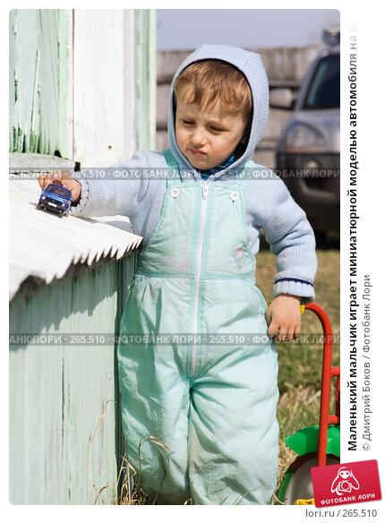 Маленький мальчик играет миниатюрной моделью автомобиля на завалинке деревенского дома, фото № 265510, снято 20 апреля 2008 г. (c) Дмитрий Боков / Фотобанк Лори