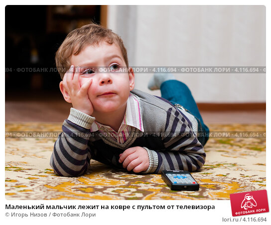 Купить «Маленький мальчик лежит на ковре с пультом от телевизора», эксклюзивное фото № 4116694, снято 13 ноября 2012 г. (c) Игорь Низов / Фотобанк Лори