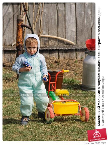 Маленький мальчик в голубом комбинезоне играет в сельском дворе с трехколесным велосипедом (2), фото № 261242, снято 20 апреля 2008 г. (c) Дмитрий Боков / Фотобанк Лори